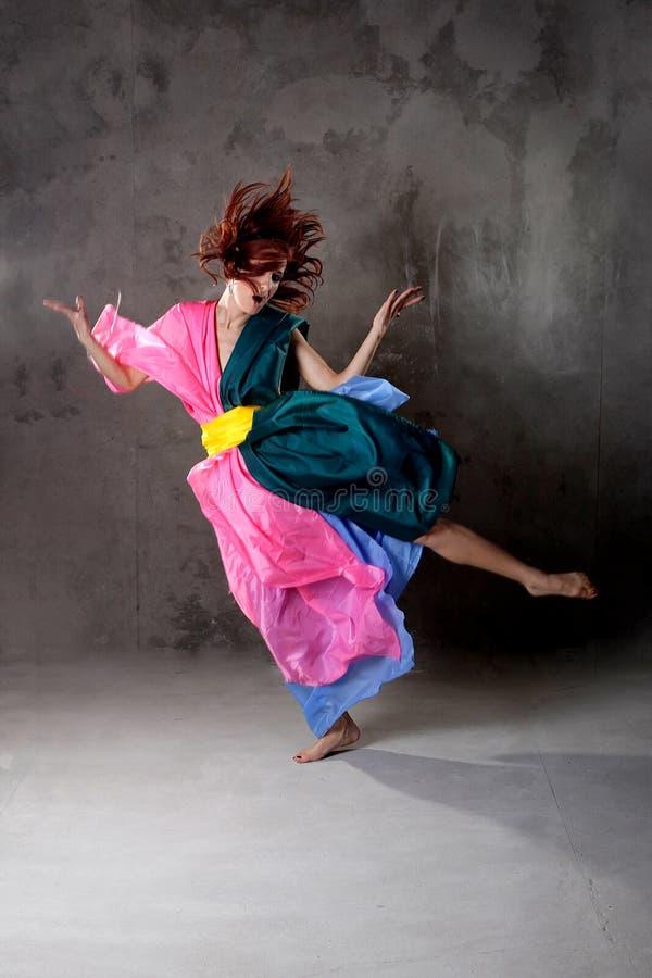 Giovane ragazza di dancing moderna in vestito variopinto immagini stock