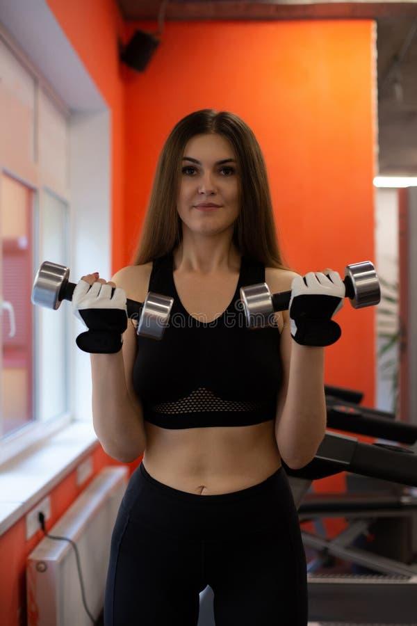 Giovane ragazza di forma fisica che fa gli esercizi con le teste di legno alla palestra fotografia stock