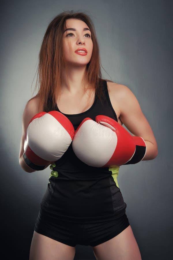 Giovane ragazza di forma fisica con i guanti bloxing che esaminano macchina fotografica sopra arte nera del fondo immagine stock libera da diritti