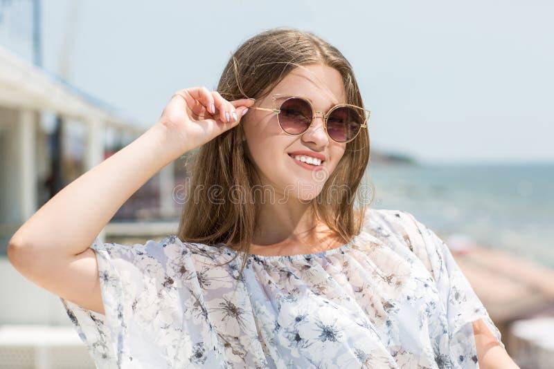 Giovane ragazza di modello affascinante e bella in vetri di sole sui precedenti del mare Un modello femminile sveglio Bella ragaz immagine stock libera da diritti