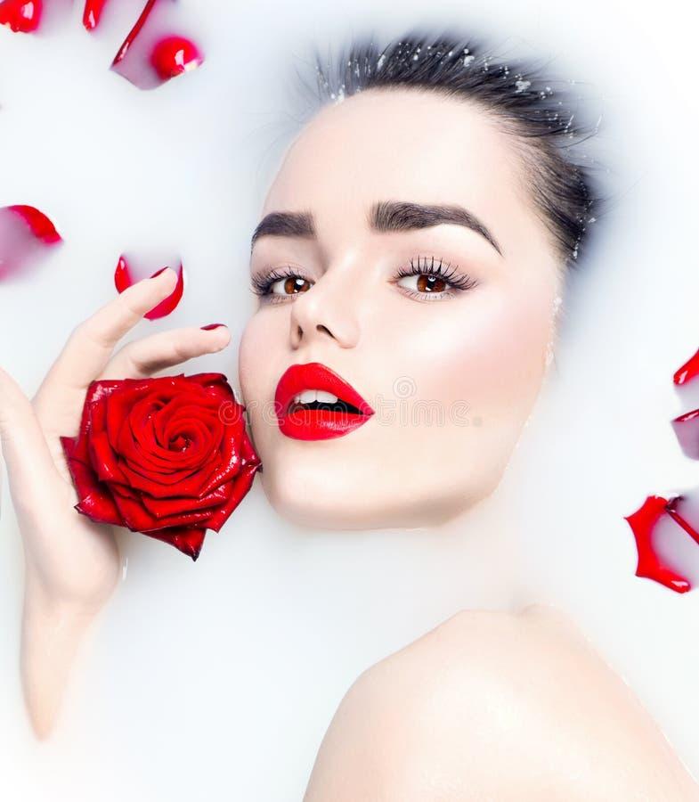 Giovane ragazza di modello di bellezza che si rilassa nel bagno del latte fotografie stock libere da diritti