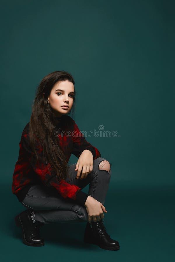 Giovane ragazza di modello teenager castana in jeans e maglietta felpata nero-rossa immagine stock
