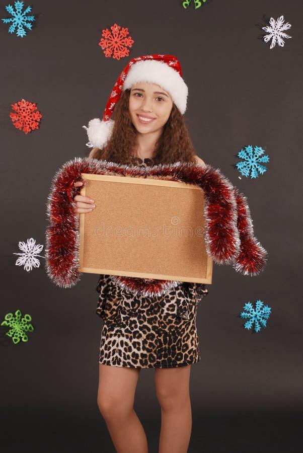Giovane ragazza di natale in cappello di Santa con il bordo in bianco del sughero fotografia stock