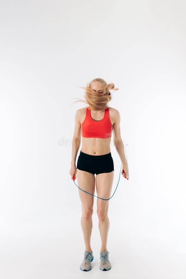 Giovane ragazza divertente con il salto della corda su fondo bianco immagini stock