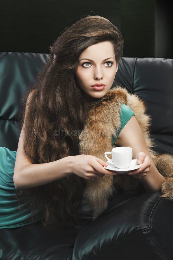 Giovane ragazza elegante nel verde con la tazza. immagine stock