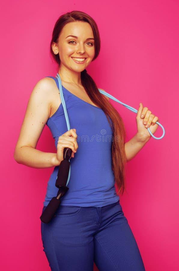 Giovane ragazza esile felice con il salto della corda sulla dolcezza sorridente del fondo rosa sveglia fotografia stock libera da diritti