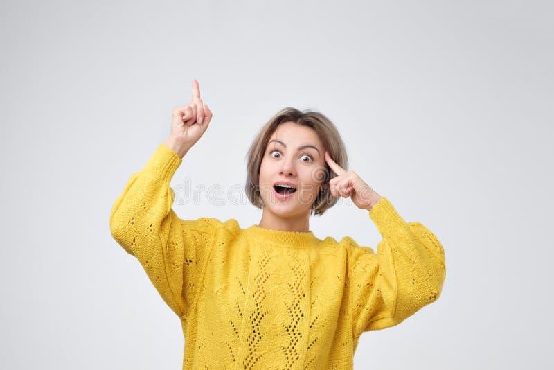 Giovane ragazza europea in maglione giallo che indica con le dita su fotografia stock
