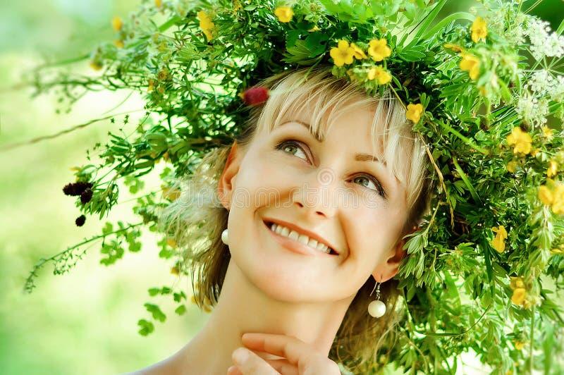 Giovane ragazza felice in corona delle erbe e dei fiori Giorno di estate in un prato fotografia stock libera da diritti