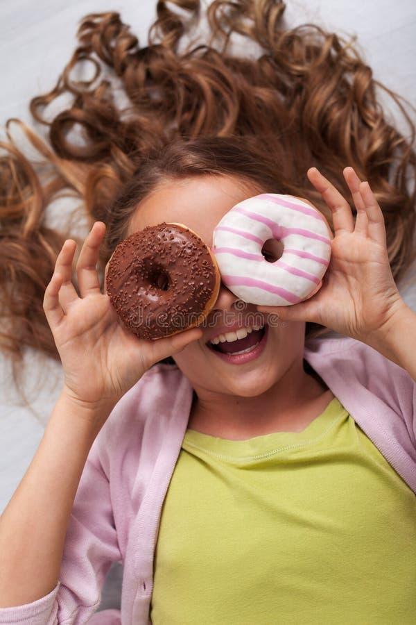 Giovane ragazza felice dell'adolescente con una risata degli occhiali di protezione della ciambella fotografie stock