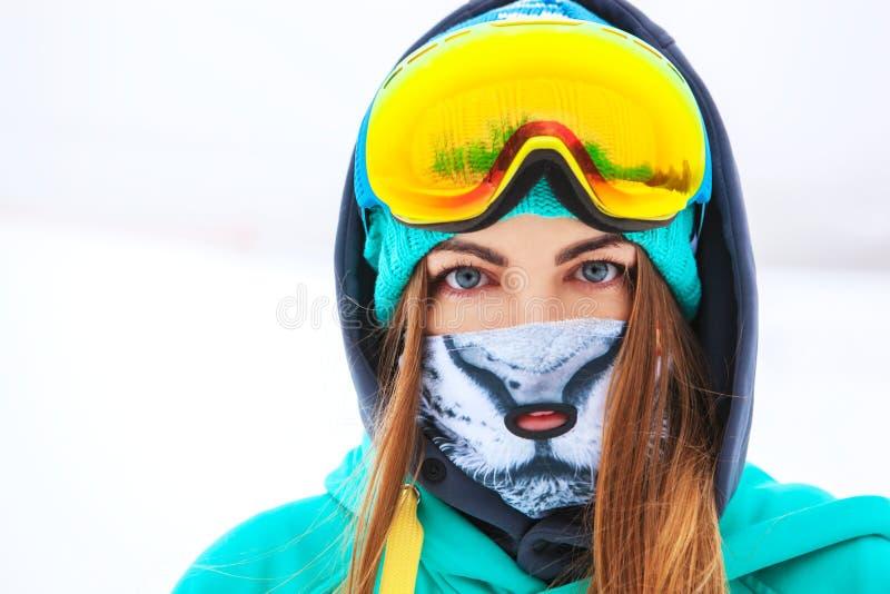 Giovane ragazza felice dello snowboarder negli occhiali di protezione dello snowboard immagini stock libere da diritti