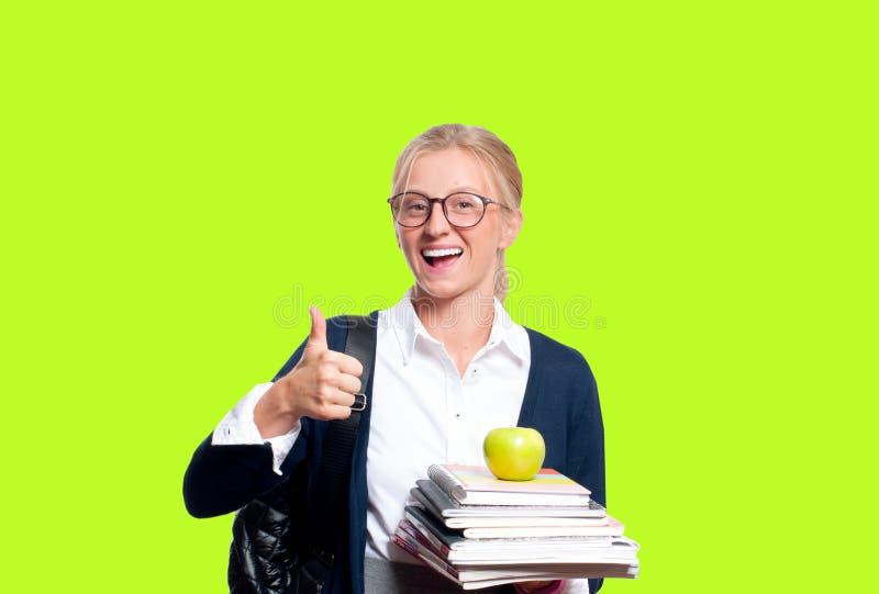 Giovane ragazza felice dello studente con i libri su fondo colorato Di nuovo al banco immagini stock