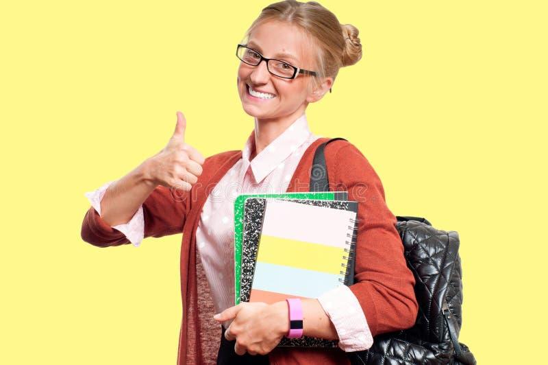 Giovane ragazza felice dello studente con i libri su fondo giallo Di nuovo al banco immagini stock