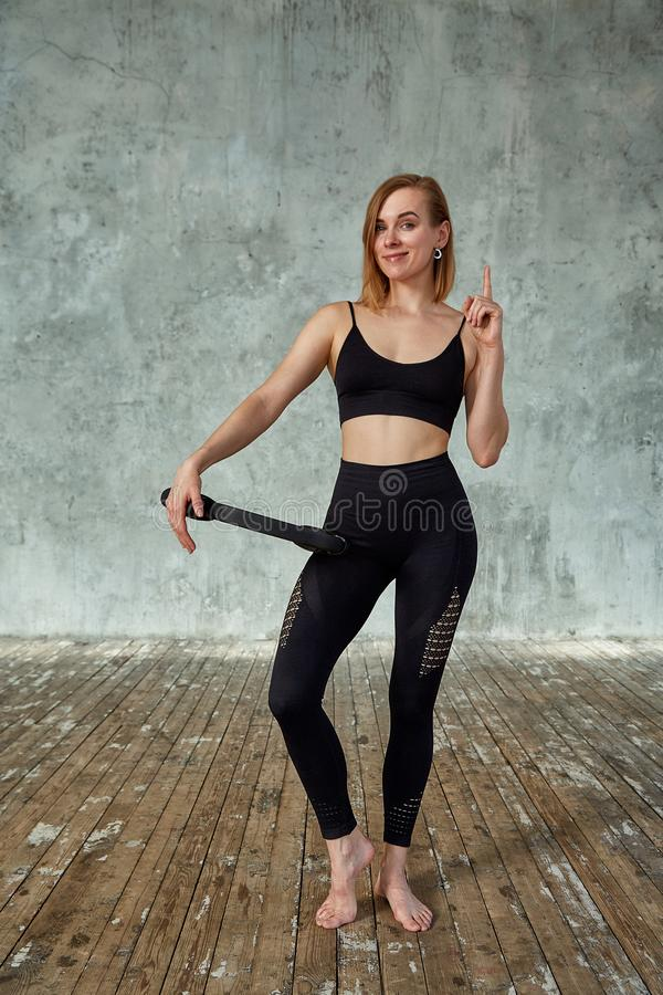 Giovane ragazza felice di forma fisica con l'ente sportivo allo studio su un fondo grigio Bella ragazza di misura Modello di form immagini stock