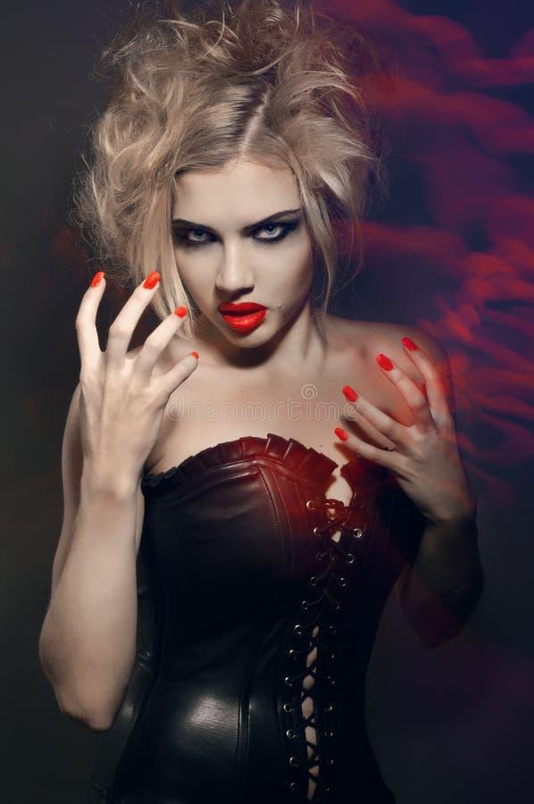 Giovane ragazza gotica con gli orli ed i chiodi rossi fotografia stock