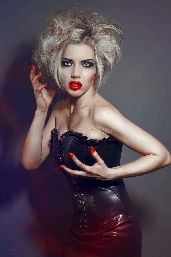 Giovane ragazza gotica con gli orli ed i chiodi rossi immagine stock libera da diritti