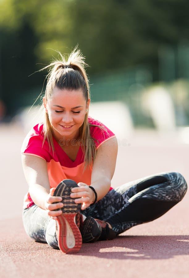Giovane ragazza graziosa che fa gli esercizi al campo di sport immagini stock libere da diritti