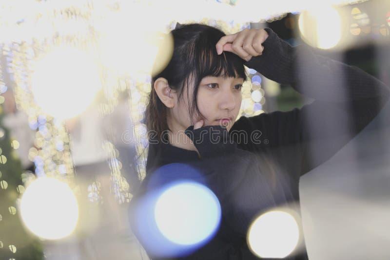 Giovane ragazza graziosa che porta la maglietta felpata nera del cotone sul fondo del bokeh alla notte fotografia stock libera da diritti