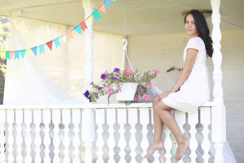 Giovane ragazza graziosa con capelli castana lunghi in vestito nero d'annata in piselli bianchi che si siedono vicino alla casa d fotografie stock