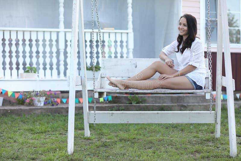Giovane ragazza graziosa con capelli castana lunghi in vestito nero d'annata in piselli bianchi che si siedono vicino alla casa d immagini stock libere da diritti