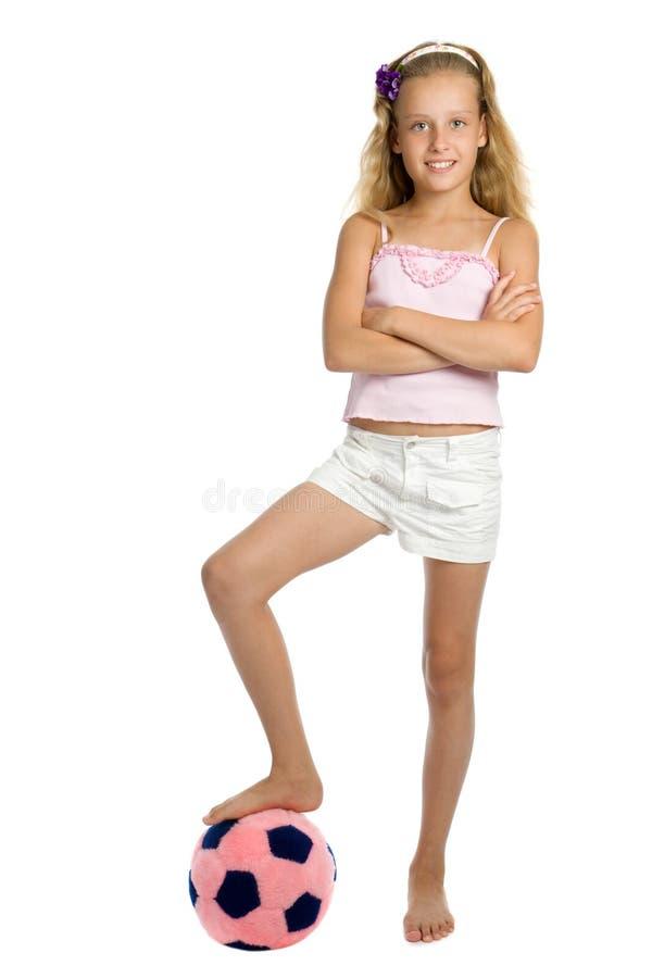 Giovane ragazza graziosa con la sfera di calcio del giocattolo fotografia stock libera da diritti