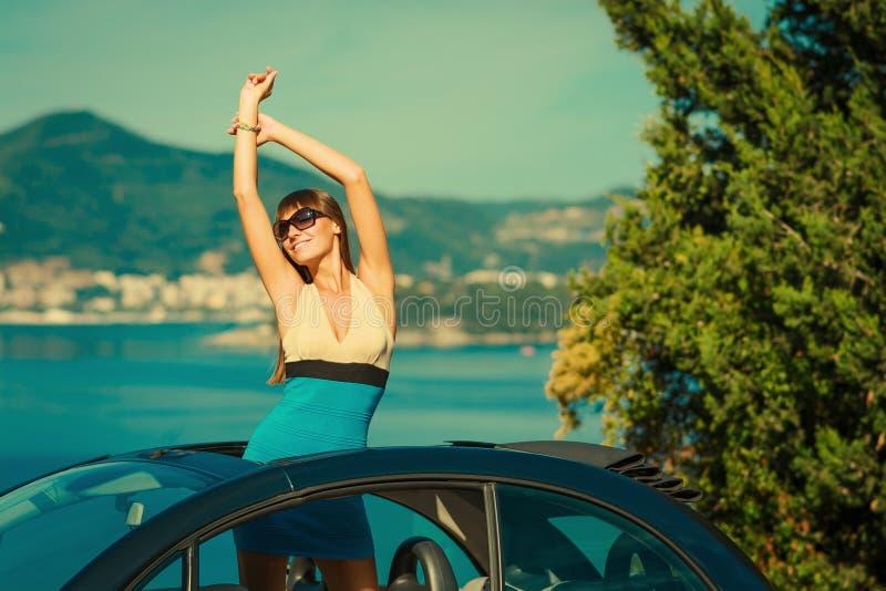 Giovane ragazza graziosa felice che gode del viaggio in loro convertibile, donna che alza armi e che sorride alla costa di mar Me fotografia stock libera da diritti