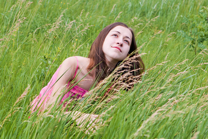 Giovane ragazza graziosa su erba fotografie stock