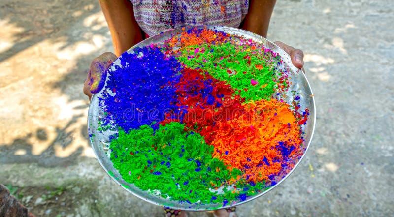 Giovane ragazza indiana che tiene i colori multipli della polvere di Holi in un piatto durante il festival dei colori o del festi immagini stock libere da diritti