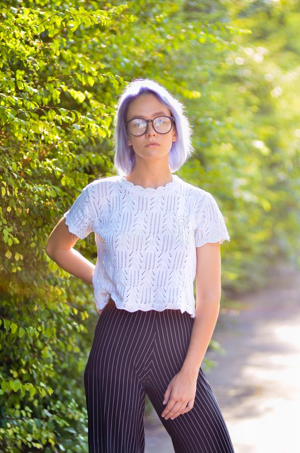 Giovane ragazza informale dei pantaloni a vita bassa con capelli porpora cinerei in vetri che posano davanti ad una macchina foto immagini stock