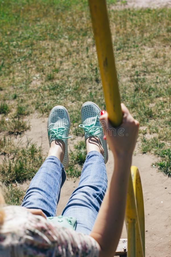 Giovane ragazza inriconoscibile con jeans blu e scarpe da tennis menta che nuotano in un albero, oscillando in una giornata pacif immagine stock libera da diritti