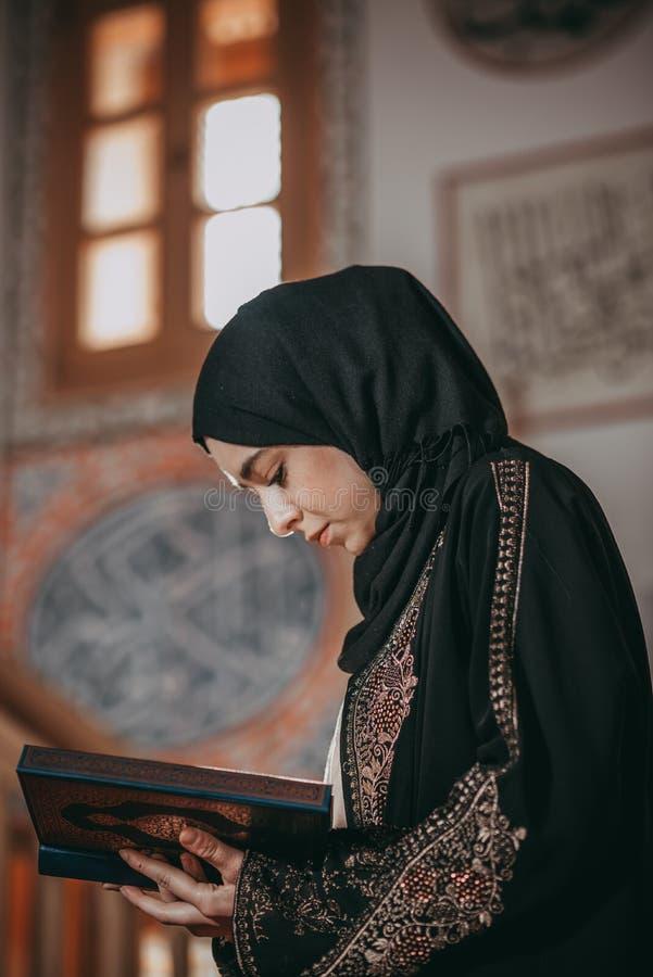 Giovane ragazza musulmana che legge un libro sacro fotografie stock