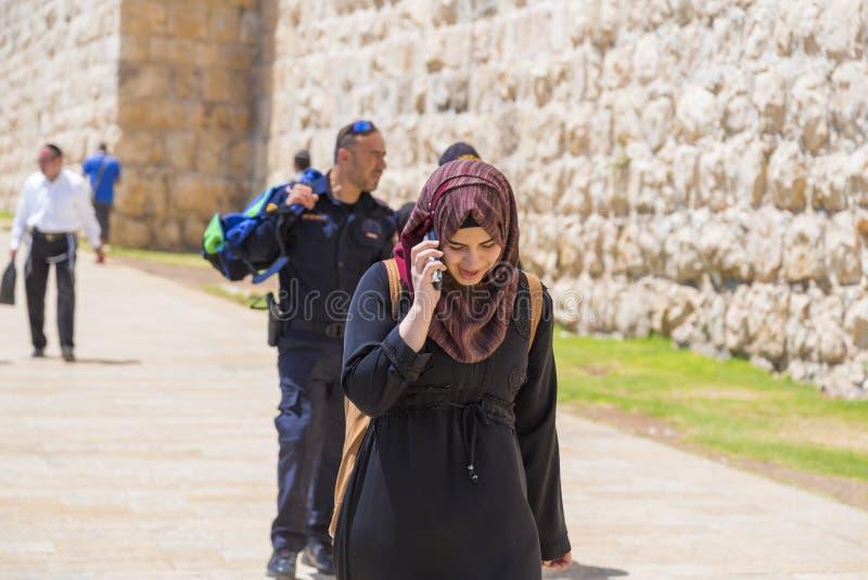 Giovane ragazza musulmana che parla sul telefono e che cammina intorno al ol fotografia stock libera da diritti