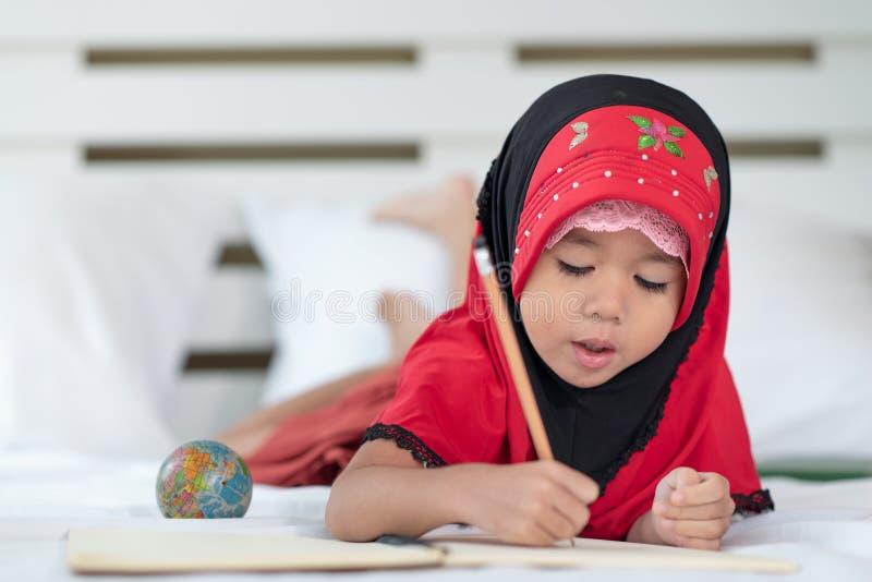 Giovane ragazza musulmana che scrive un libro, bambino islamico per fare compito a casa immagini stock libere da diritti