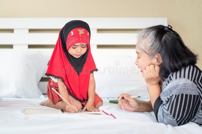 Giovane ragazza musulmana che scrive un libro con la nonna, bambino islamico per fare compito a casa immagini stock libere da diritti