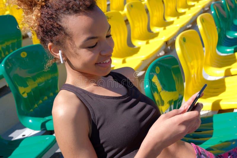 Giovane ragazza nera allegra sexy che si siede da solo su una poltrona per gli spettatori allo stadio Airpods bianco nell'orecchi fotografia stock libera da diritti