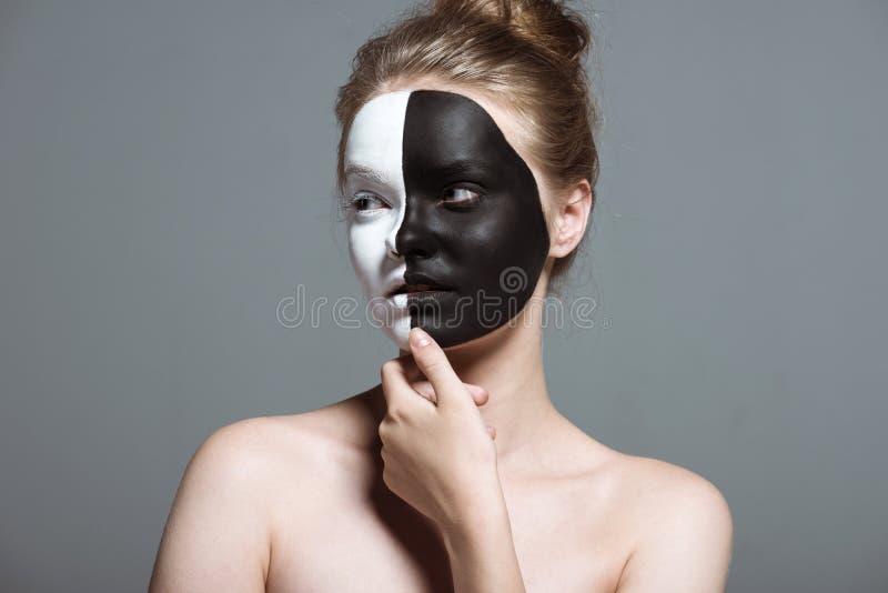 giovane ragazza pensierosa con bodyart bianco e nero creativo sul fronte, fotografie stock