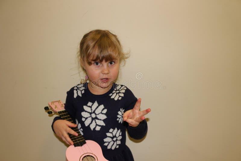 Giovane ragazza prescolare che impara giocare le ukulele immagini stock libere da diritti
