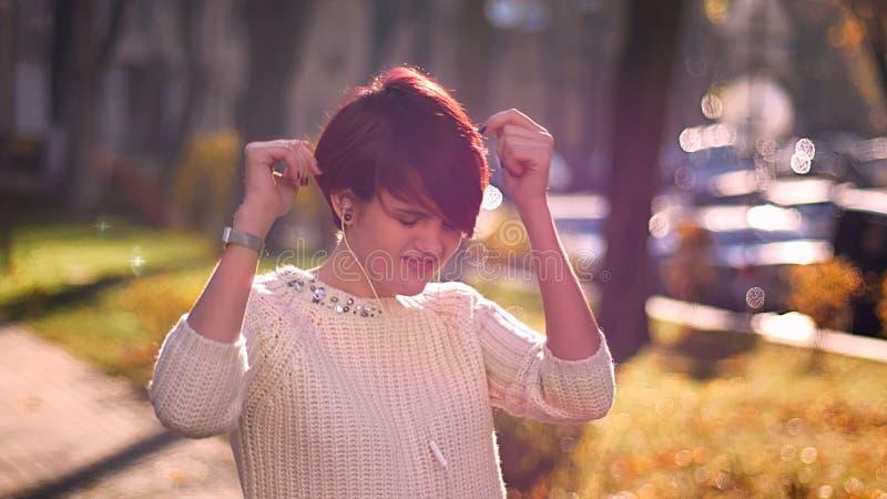 Giovane ragazza rosa-dai capelli caucasica con le cuffie che ascolta la musica e che balla felicemente sul fondo soleggiato del p fotografia stock