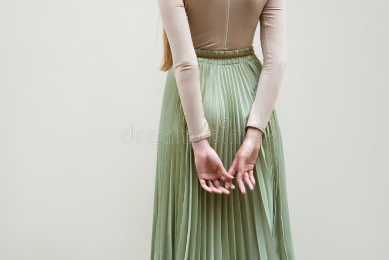 Giovane ragazza rossa dei capelli in cappello, vestito in gonna beige delle pieghe del turchese e della blusa, sul backgraund leg immagine stock