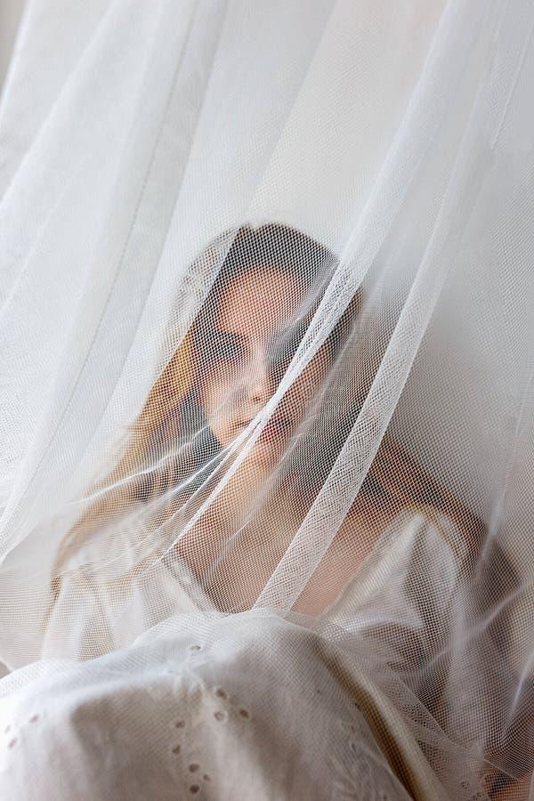 Giovane ragazza sensuale graziosa in vestito bianco che si nasconde dietro la tenda Concetto nascosto di bellezza fotografia stock