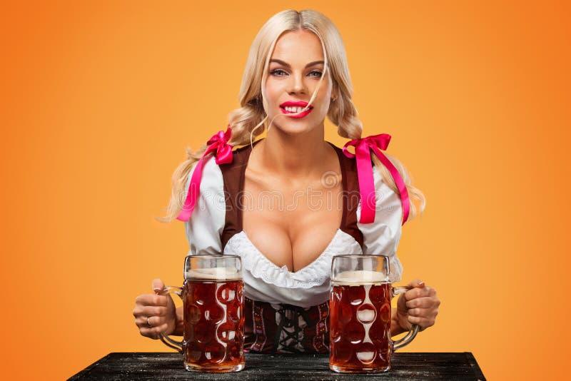 Giovane ragazza sexy di Oktoberfest - cameriera di bar, portando un vestito bavarese tradizionale, grandi tazze di birra serventi fotografie stock