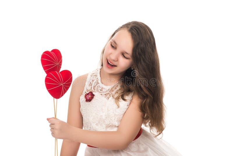 Giovane ragazza sorridente con cuori rossi nelle mani, isolate su bianco fotografia stock libera da diritti