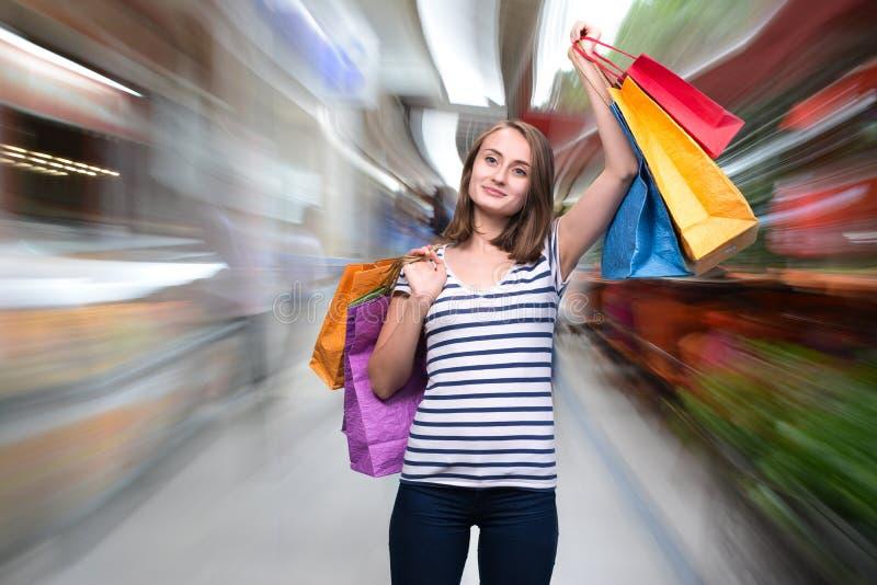 Giovane ragazza sorridente con i sacchetti della spesa fotografia stock