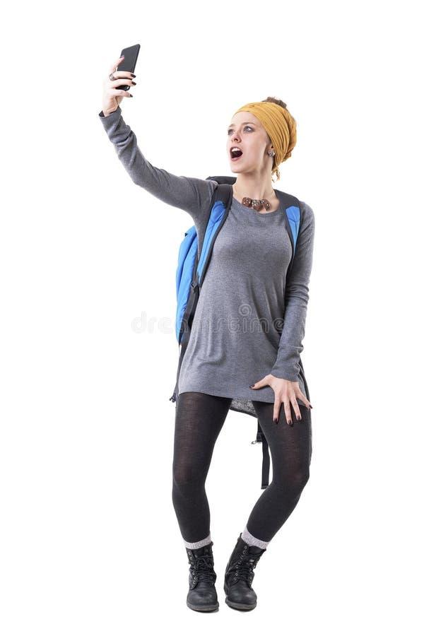 Giovane ragazza spensierata allegra fresca del viaggiatore dei pantaloni a vita bassa che prende grida del selfie dell'eccitazion immagini stock libere da diritti