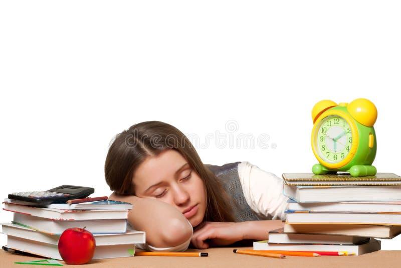 Giovane ragazza stanca dello studente che dorme sulla tavola fotografie stock