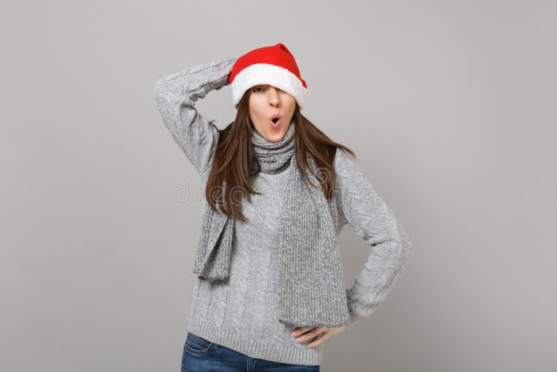 Giovane ragazza stupita divertente di Santa in maglione, occhio della copertura della sciarpa con il cappello di Natale, tenente  fotografie stock libere da diritti