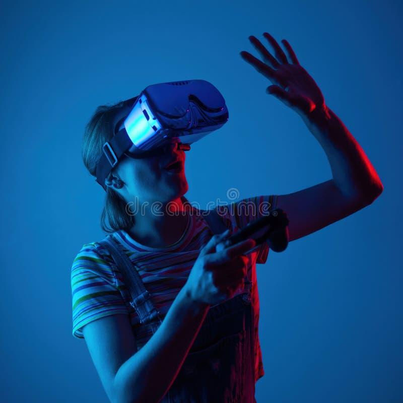 Giovane ragazza sveglia che gioca vr con gamepad con luce blu-rossa creativa Emocyanally e divertimento gioco di concetto fotografia stock
