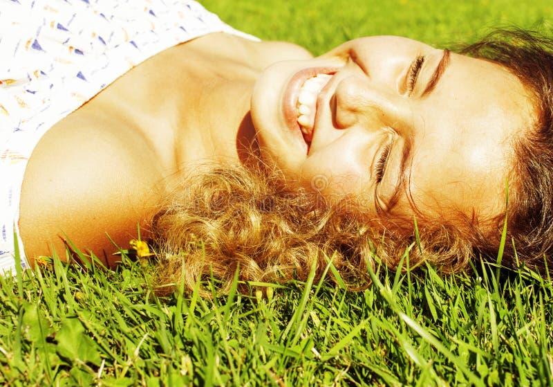 Giovane ragazza sveglia di estate sulla fine sorridente felice di rilassamento esterna dell'erba verde su, concetto della gente d fotografia stock