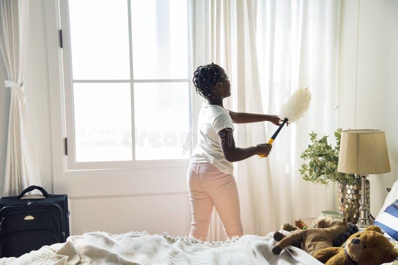 Giovane ragazza teenager che pulisce la camera da letto fotografie stock libere da diritti