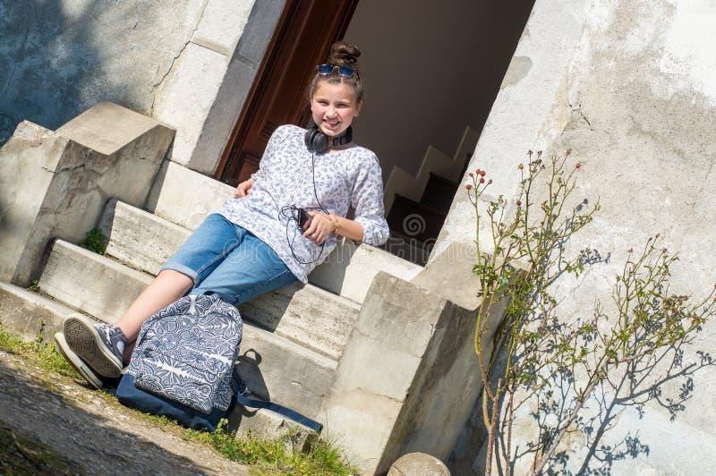 Giovane ragazza teenager sorridente che si siede sui punti immagini stock