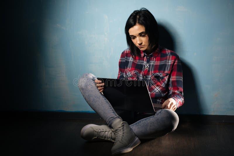 Giovane ragazza triste che soffre dalla dipendenza dalle reti sociali che si siedono sul pavimento con un taccuino fotografia stock libera da diritti